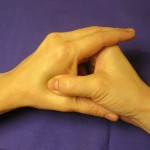 Using your thumb, massage the pressure point between the index finger and thumb.