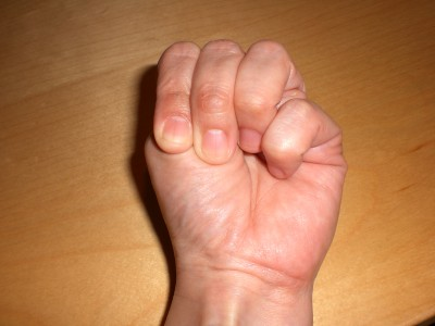 Thumb is between ring finger and pinky